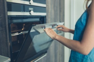 A young woman is opening the oven in her modern kitchen